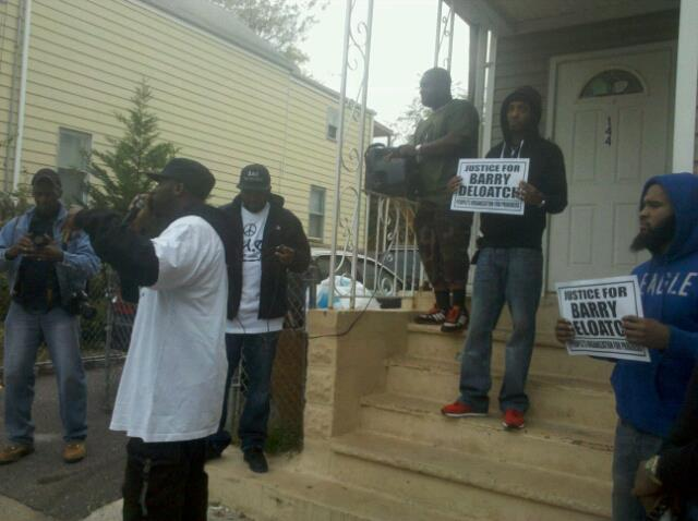 Barry Deloatch's two sons stand on the porch where his father encountered the police officers who shot and killed him.