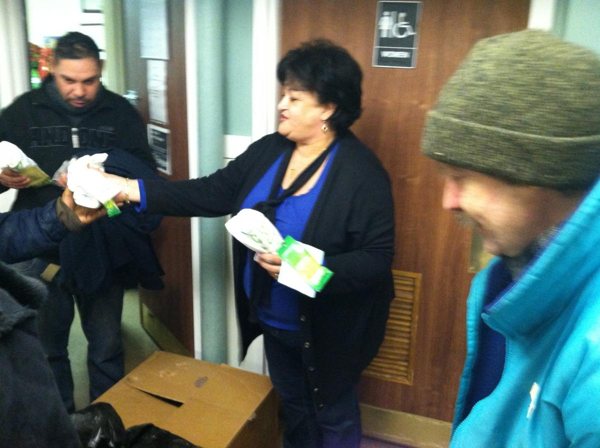 A woman distributes hygiene products to homeless individuals at Elijah's Promise.